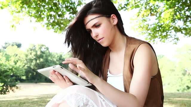Outdoors with a digital tablet.