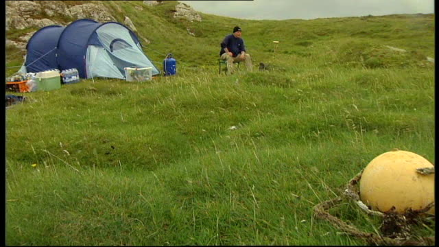 outer hebrides: scaravay : ext various of geoff spice camping on island geoff spice interview sot spice washing dishes in washing up bowl on grass... - hebrides stock videos & royalty-free footage