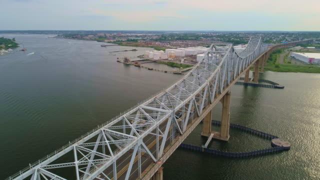 vidéos et rushes de outerbridge crossing bridge mène à la zone industrielle de new jersy de staten island à travers le détroit de marée arthur kill et la frontière de l'état. drone-pris vidéo aérienne avec le cinématique vers l'arrière et panoramique avec le mo - pont
