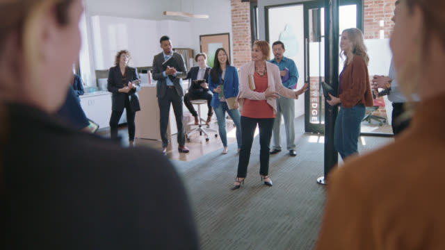 outgoing businesswoman leads a positive team celebration with clapping and congratulating for a fellow employee - employee stock videos & royalty-free footage