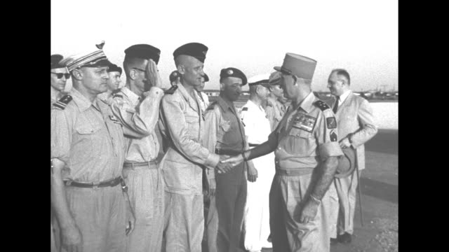 Outgoing Supreme Commander of French Far East Expeditionary Force General Raoul Salan inspects troops lined up on tarmac in Laos shakes hands with...