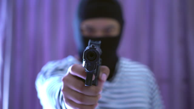 outlaw bad man holds a gun pointing the target, robber in black hood holding a gun and pointing to a victim. - gunman stock videos and b-roll footage