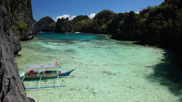 """""""ws outrigger boat anchored in idyllic tropical inlet surrounded by plants and sharp limestone cliffs / small lagoon, miniloc island, bacuit archipelago, el nido, palawan, philippines"""" - inlet stock videos and b-roll footage"""