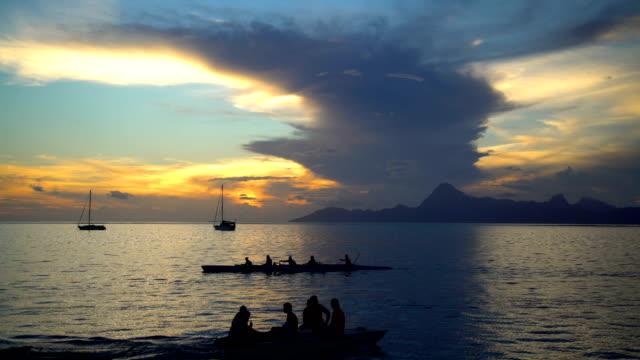 outrigger canoe moorea island from tahiti at sunset - polynesischer abstammung stock-videos und b-roll-filmmaterial