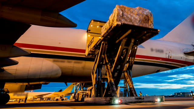 outside cargo plane loading with twilight sky - panning - mezzo di trasporto video stock e b–roll