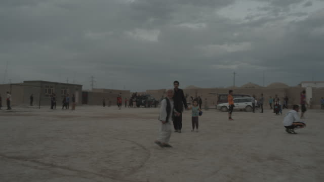 outskirt of herat, afghanistan, kids and adult playing football - afghanistan stock videos & royalty-free footage