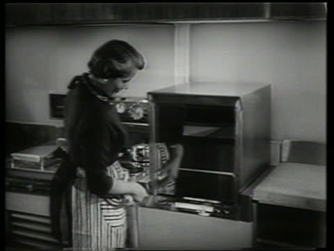 B/W oven raises / woman pushes button to open it / 'Kitchen of tomorrow' / SOUND