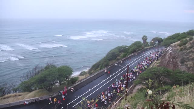over 25000 runners take on 262 miles with a predawn start with festive entertainment mass up diamond head hill with pacific ocean in background then... - salmini stock videos and b-roll footage