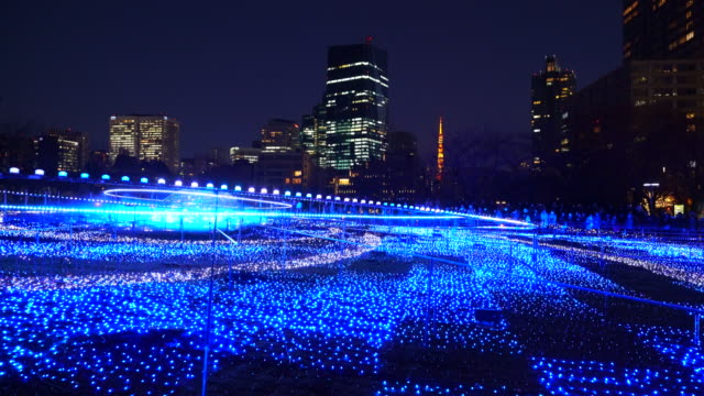 over 500,000 led lights are displayed in the starlight garden (grass square) and glow in the night in roppongi tokyo on december 21 2017. people are watching and photographing illumination. - tokyo midtown stock videos and b-roll footage