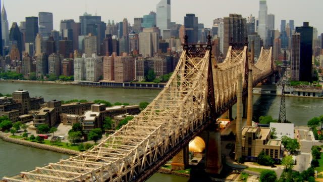 aerial pov over 59th street bridge from queens to roosevelt island to manhattan with view of midtown - queens stock-videos und b-roll-filmmaterial