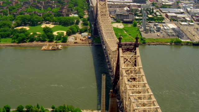 AERIAL POV over 59th Street Bridge from Roosevelt Island to Queens with traffic over East River