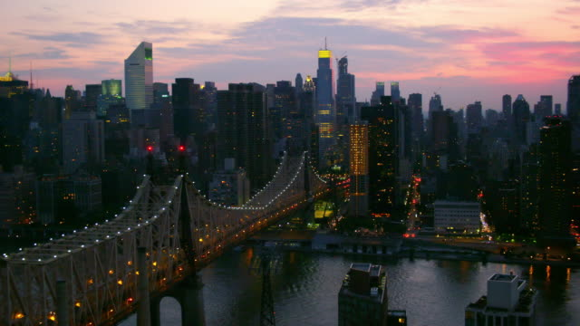 medium aerial pov over 59th street bridge to midtown manhattan cityscape at twilight - queensboro bridge stock videos & royalty-free footage