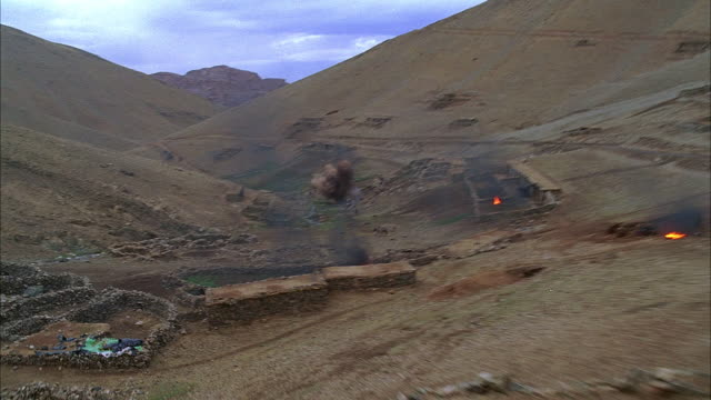 aerial reenactment over afghani village as it's being attacked by soviet fire/ refugees fleeing/ road with burning car/ morocco - afghanistan stock videos & royalty-free footage