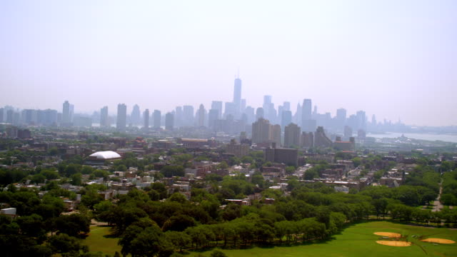 AERIAL POV over baseball fields and urban neighborhoods toward Jersey City and Manhattan skyline in background