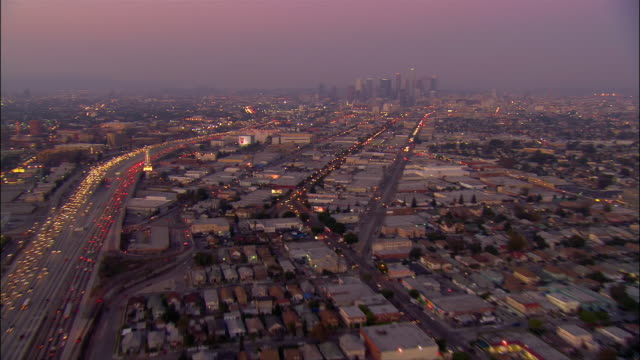 aerial over buildings and freeways towards downtown los angeles at dusk / california - usバンクタワー点の映像素材/bロール