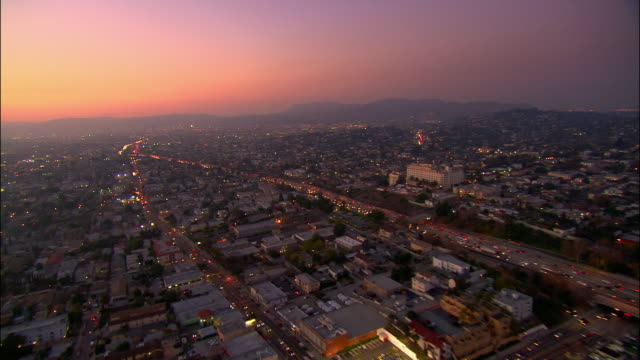 AERIAL Over buildings and freeways towards Hollywood Hills at dusk / Los Angeles, California