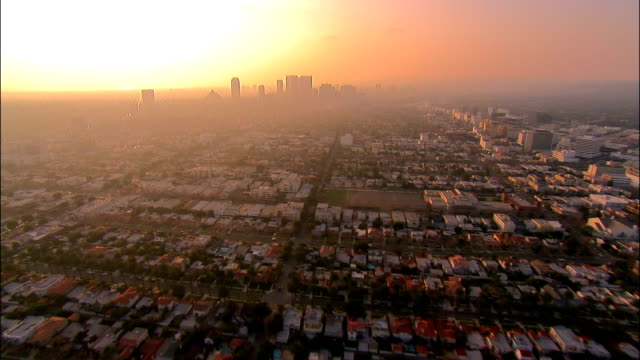 AERIAL Over buildings in central Los Angeles towards downtown in late afternoon smog / California