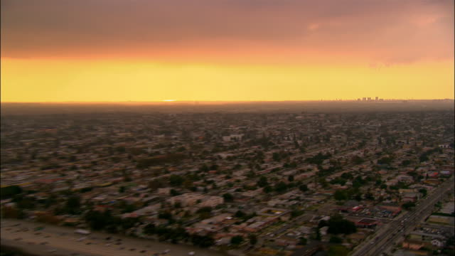 aerial over buildings in long beach with silhouette of compton / woodley airport on horizon at twilight / pull out to view of freeway in foreground / california - long beach california video stock e b–roll