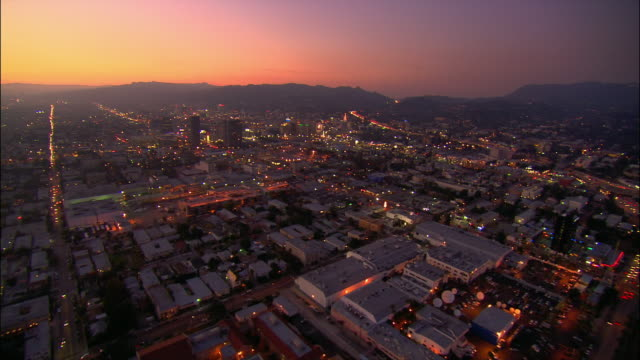 AERIAL Over buildings towards Hollywood Hills at dusk / Los Angeles, California