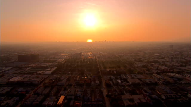 AERIAL Over central Los Angeles towards Pacific horizon at sunset / California