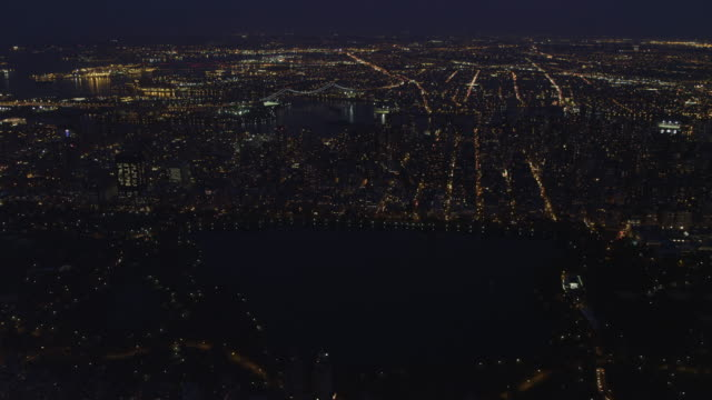 over central park in new york city at night, looking toward upper east side and robert f. kennedy bridge. shot in november 2011. - artbeats video stock e b–roll