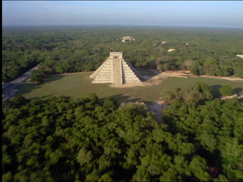 aerial over chichen itza pyramid temple ruins surrounded by forest / yucatan, mexico - chichen itza stock videos and b-roll footage