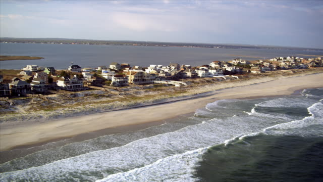 aerial over coastline homes beaches and sky / hamptons, new york - long island video stock e b–roll
