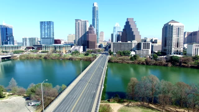 over congress bridge colorful blue sky day moving towards texas state capitol through austin texas skyline - austin texas video stock e b–roll