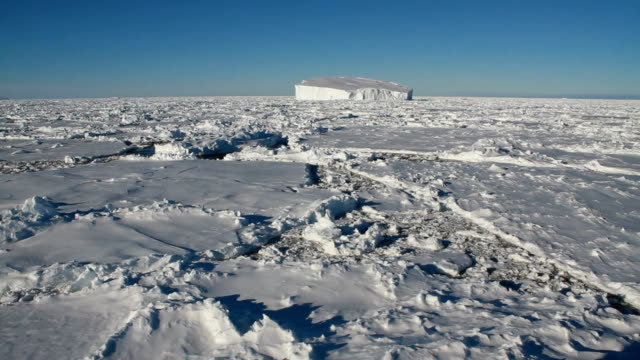 pan over cracked ice with iceberg in the distance, antarctica - antarctica aerial stock videos & royalty-free footage