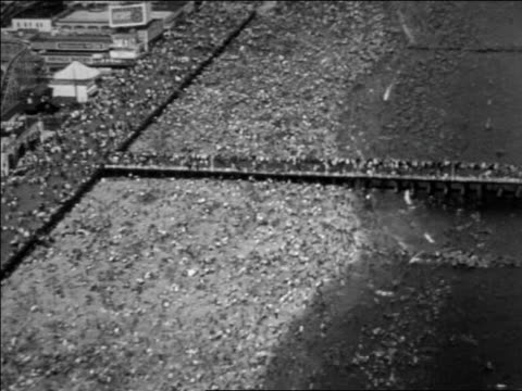 b/w 1930 aerial over crowded beach + boardwalk at coney island / nyc / documentary - coney island brooklyn stock videos & royalty-free footage