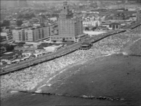 b/w 1930 aerial over crowded beach + buildings at coney island / nyc / documentary - 1930 stock videos & royalty-free footage