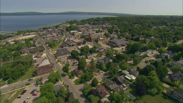 vídeos de stock, filmes e b-roll de aerial over downtown area and suburbs moving toward lake michigan/ petoskey, mi - michigan