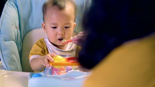 食べる以上: スプーンで離乳食を食べる赤ちゃん。 - 幼児点の映像素材/bロール