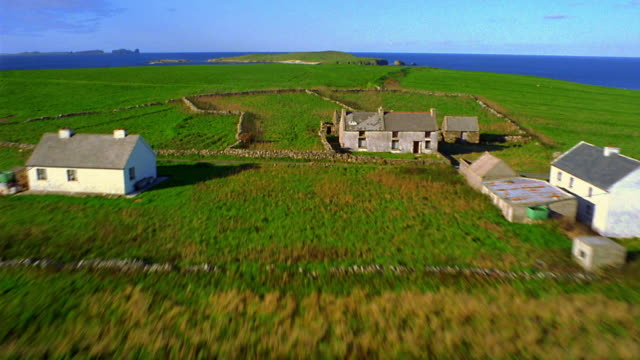 aerial over farmland + houses with islands + sea in background / ireland - farmhouse stock videos & royalty-free footage