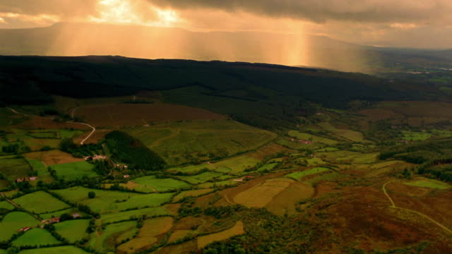 vidéos et rushes de aerial over farmland with mountains + orange sky in background / ireland - patchwork landscape
