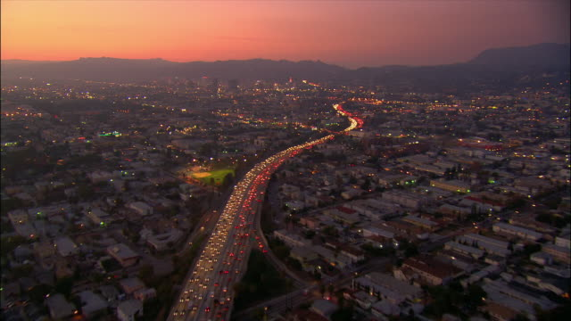 AERIAL Over  freeway towards Hollywood Hills at dusk / Los Angeles, California