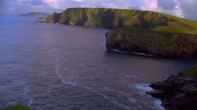 vidéos et rushes de aerial over grass covered cliffs with green cliffs + ocean in background / ireland - irlande