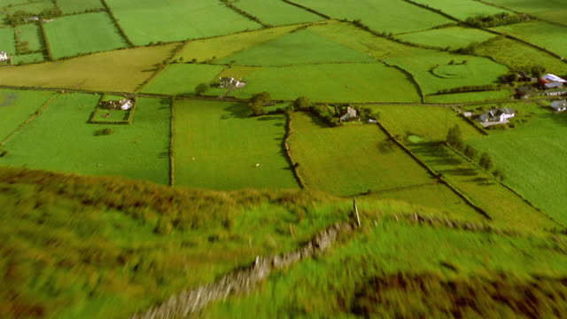AERIAL over green field to large mound over cliff edge towards farmland / water in background / Ireland