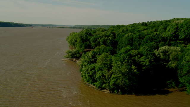 AERIAL POV over green trees and houses along Hudson River
