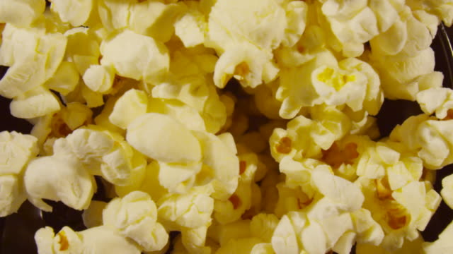over head shot of popcorn rising out of a popping machine. - popcorn stock-videos und b-roll-filmmaterial