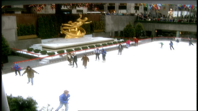 vídeos de stock, filmes e b-roll de over head shot of tourists ice skating at rockefeller center - pista de patinação no gelo