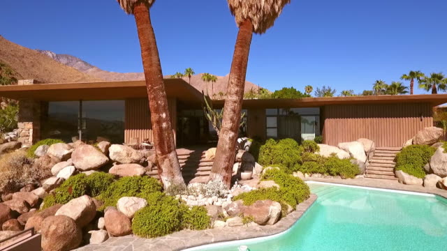 ts over hedges of bougainvillea to swimming pool and back side of modernism style 1954 home built into a hillside - palm springs california stock videos & royalty-free footage