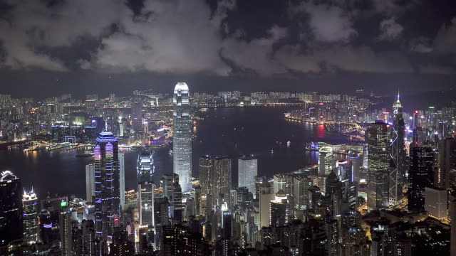 T/L over Hong Kong Island at night during famous nightly light show, High angle view from Victoria Peak, Mount Austin, across harbour towards Kowloon