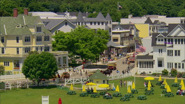 AERIAL Over hotels, people in park, and horse-drawn wagons on Main Street/ Mackinac Island, Michigan