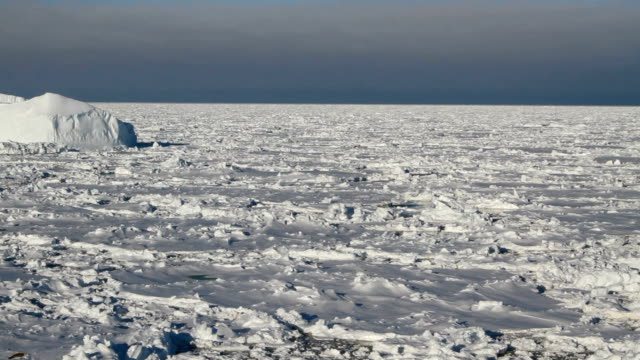 pan over ice covered ocean with iceberg, antarctica - antarctica stock videos and b-roll footage