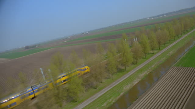aerial over intercity train going thru green farmland / leiden, holland - passenger train stock videos & royalty-free footage