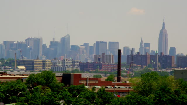 AERIAL SIDE POV over low buildings in New Jersey with Midtown Manhattan skyline in background
