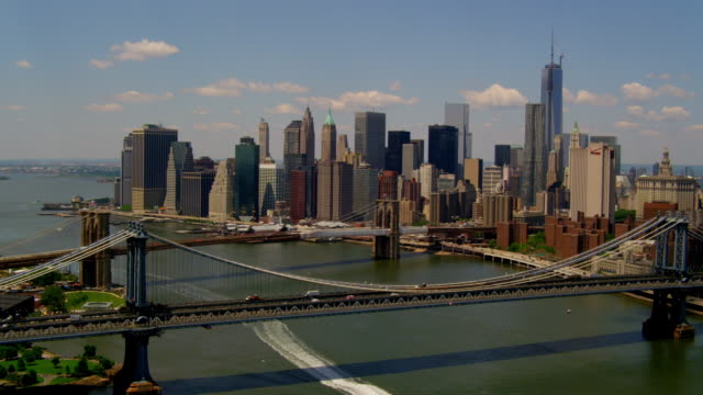 WIDE AERIAL POV over Manhattan and Brooklyn Bridges to Financial District