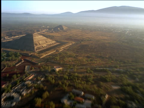 AERIAL over Mayan Pyramid of the Sun + ruins + city / mountains in background / Teotihuacan, Mexico