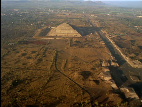 AERIAL over Mayan Pyramid of the Sun + ruins / mountains in background / Teotihuacan, Mexico
